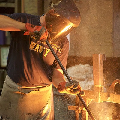 Dakota Foundry worker pouring molten iron into mold
