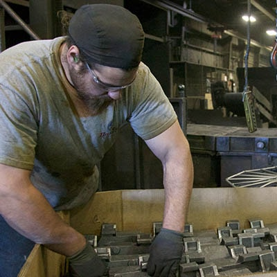 Dakota Foundry worker packing cast parts for shipping